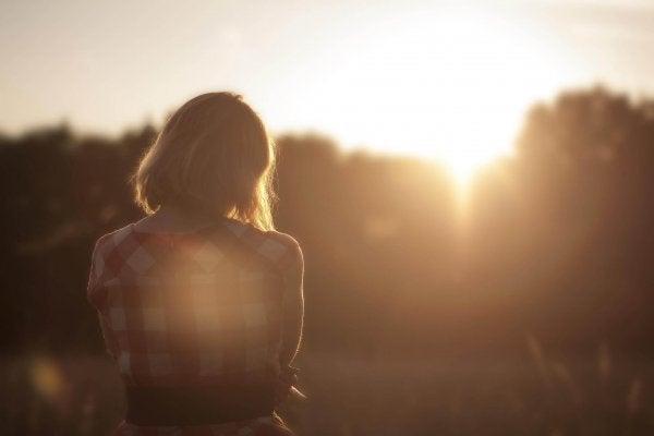 Kvinde står alene på mark og ser solnedgang