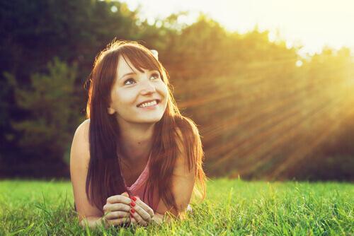 Smilende kvinde på græs er vejledt af pragmatisk optimisme