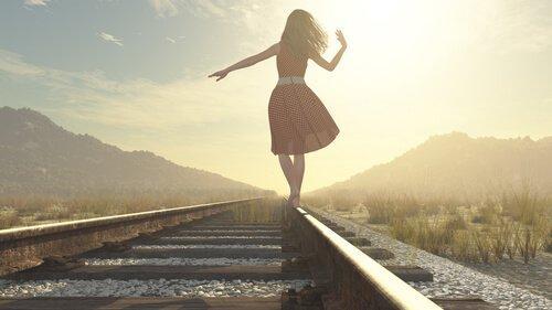 Kvinde går på togskinner blandt bjerge