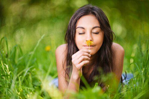 Kvinde, der smiler og dufter til en blomst