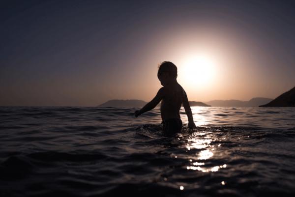 Et barn bader i havet