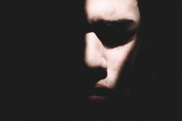 En mands ansigt lyses halvt op i mørke