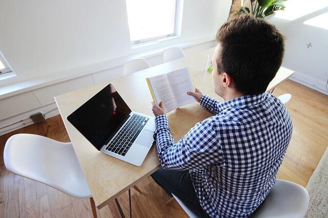 Mand læser bog på arbejde grundet arbejdsrelateret sygenærvær