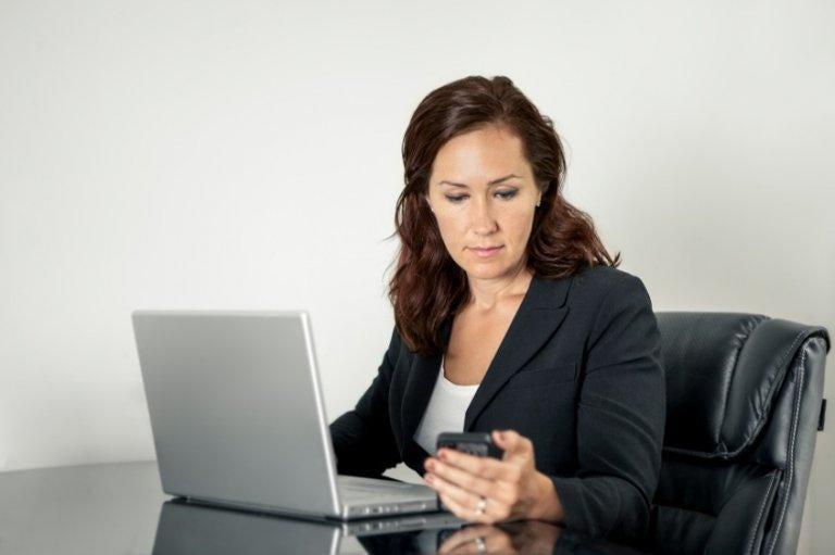kvinde tjekker lige sin mobil på arbejdet