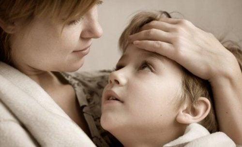 En mor holder sit barn tæt ind til sig, da det er normalt for forældre at beskytte sine børn