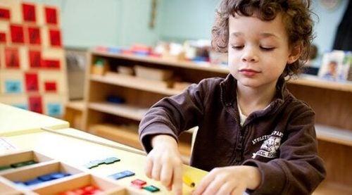 Dreng, der leger under Montessori metodens indflydelse på en skole