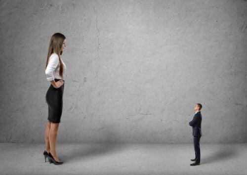 Stor kvinde ser ned på lille mand