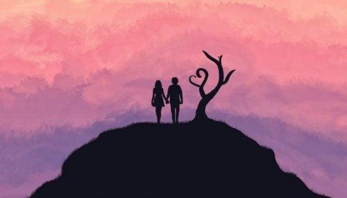 Et par står på toppen af et bjerg foran lilla himmel