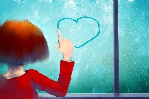 En pige, der tegner et hjerte på et vindue