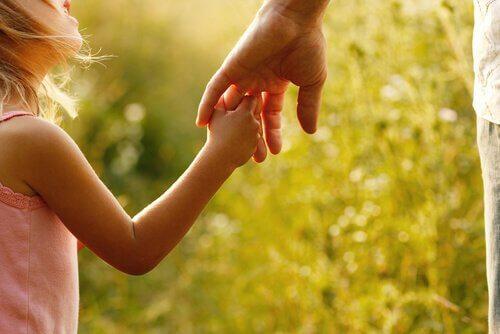 Pige holder voksen i hånden
