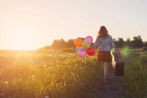 Pige, der går med balloner og en kuffert på en mark