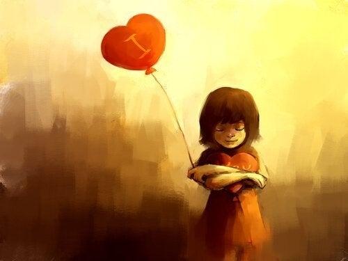En pige holder et hjerte og har en hjerteballon