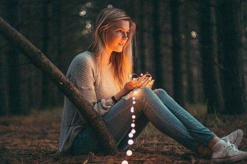 en pige med lys i en skov