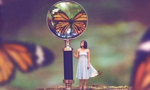 En lille pige ved siden af et forstørrelsesglas der viser en sommerfugl