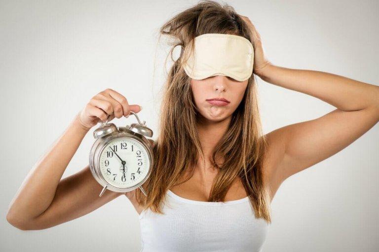 Kvinde med sovemaske og vækkeur