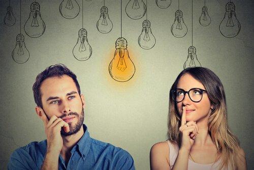 Mand og kvinde kigger betænksomt på lysende pære