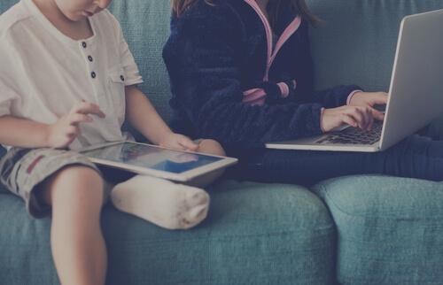 Børn på sofa med teknologi