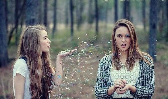Pige puster glimmer på veninde i skov