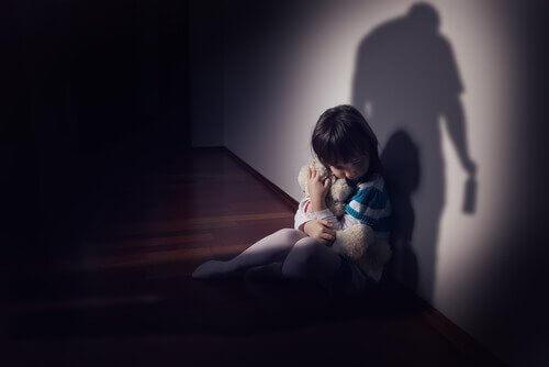 Trist barn, der holder sin bamse af frygt for sin forælder