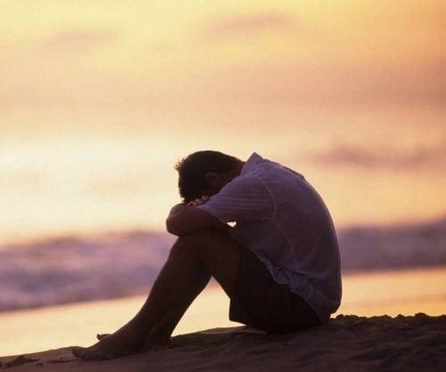 Ulykkelig mand hviler hoved på knæ