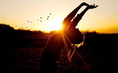 Kvinde med armene i vejret prøver at forbedre en dårlig dag