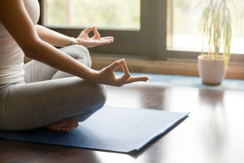 Kvinde mediterer i hendes rum dedikeret til meditation
