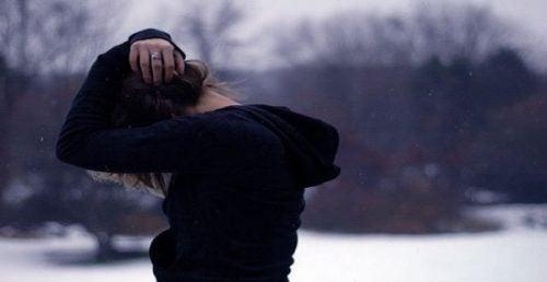 Kvinde med hoved gemt under arme oplever følelsesmæssig ræsonnement