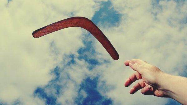 Hånd rækker ud mod boomerang på himmel