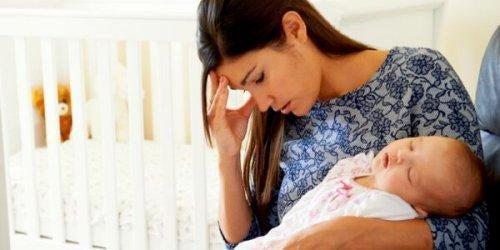 Mor med sovende baby tager sig til hoved