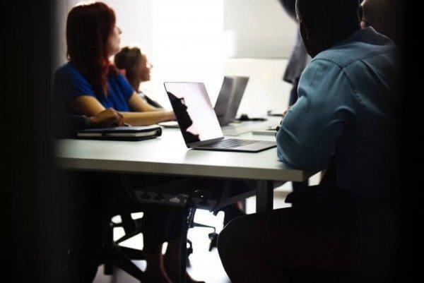 Medarbejdere sidder i møde for at opnå fremragende ledelse