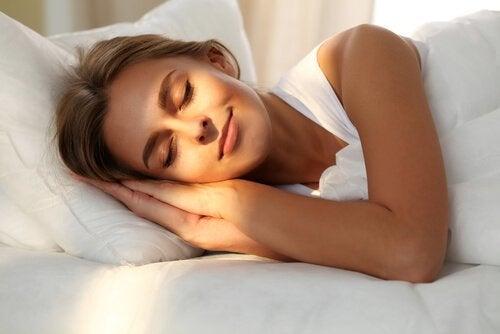 Kvinde nyder søvn i seng