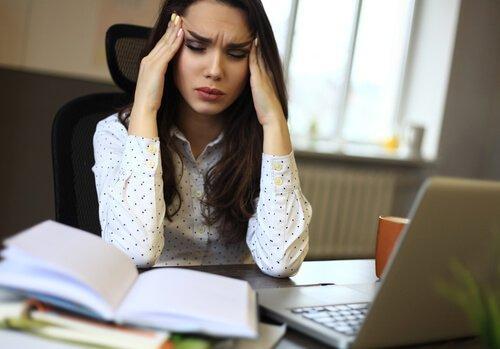 kvinde, der tager sig til hoved, har stress