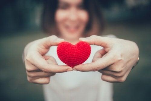 Kvinde holder hjerte i hænderne og smiler