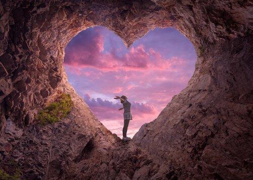 Kvinde står i hul i bjerg, der er formet som hjerte
