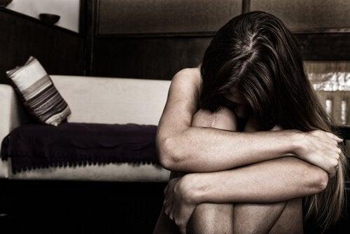 En såret kvinde lægger hoved på knæ