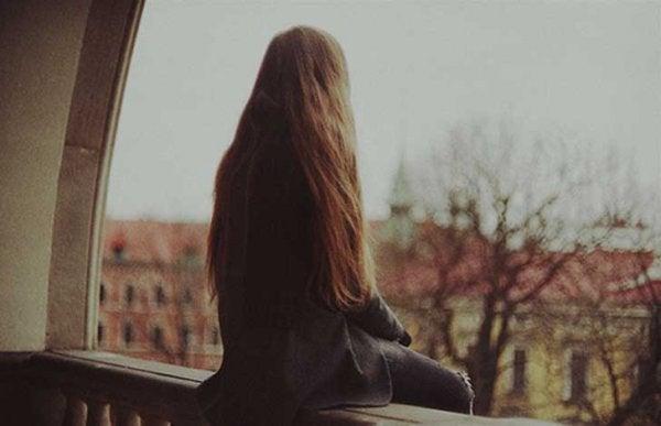 Kvinde sidder på balkon og føler sig ensom alene