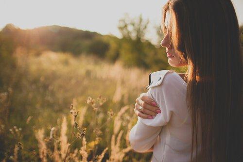Kvinde krammer sig selv på eng
