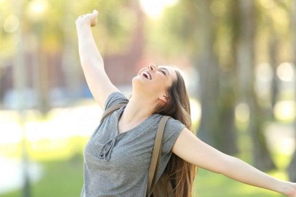 Pige med stor selvværd strækker armene ud i lykke