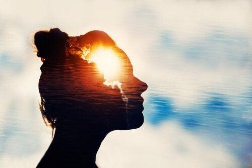 Silhuet af kvinde med lys i panden som symbol for mentale øvelser til lykke