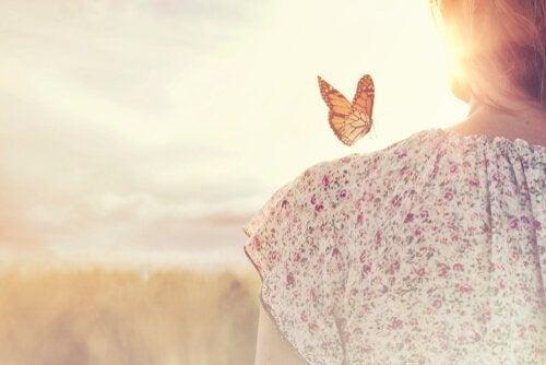 Kvinde med sommerfugl på skulderen, der symboliserer en af de 10 love for overflod.