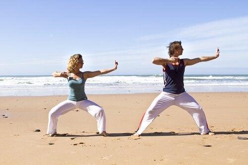 kvinde og mand dyrker qigong på stranden