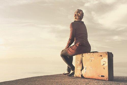 kvinde sidder klar på sin kuffert