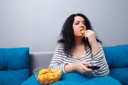 Kvinde, der spiser chips, fører stillesiddende livsstil
