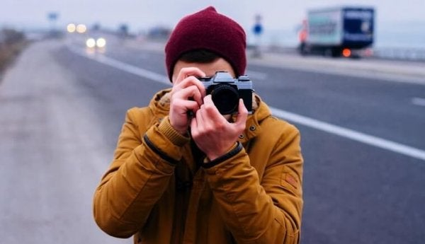 mand tager fotos på vej