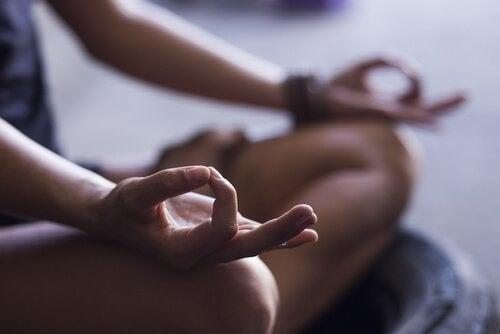 Person mediterer i skrædderstilling