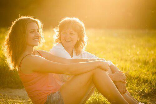 Mor og datter på eng i sollys