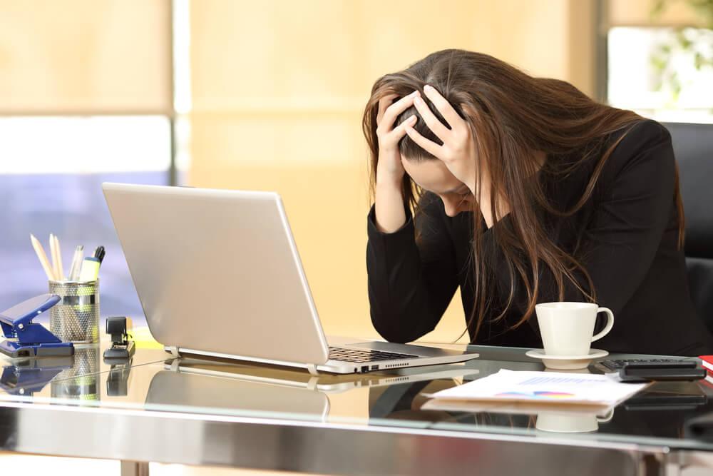 Kvinde på kontor oplever de forskellige bivirkninger ved arbejdsrelateret stress