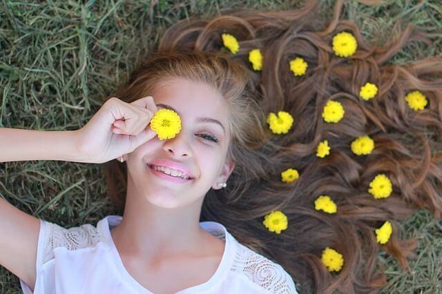 pige i græs med blomster i håret