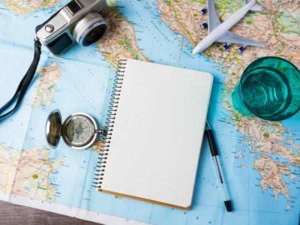 Blank notesbog ovenpå verdenskort med kamera, kompas, vandglas og fly
