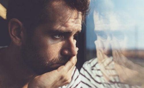 Trist mand, der kigger ud af vinduet, symboliserer de forskellige stadier af sorg